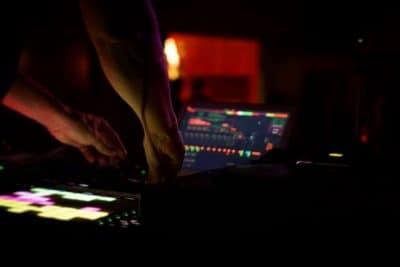 mies soittaa elektronista musiikkia laitteistolla