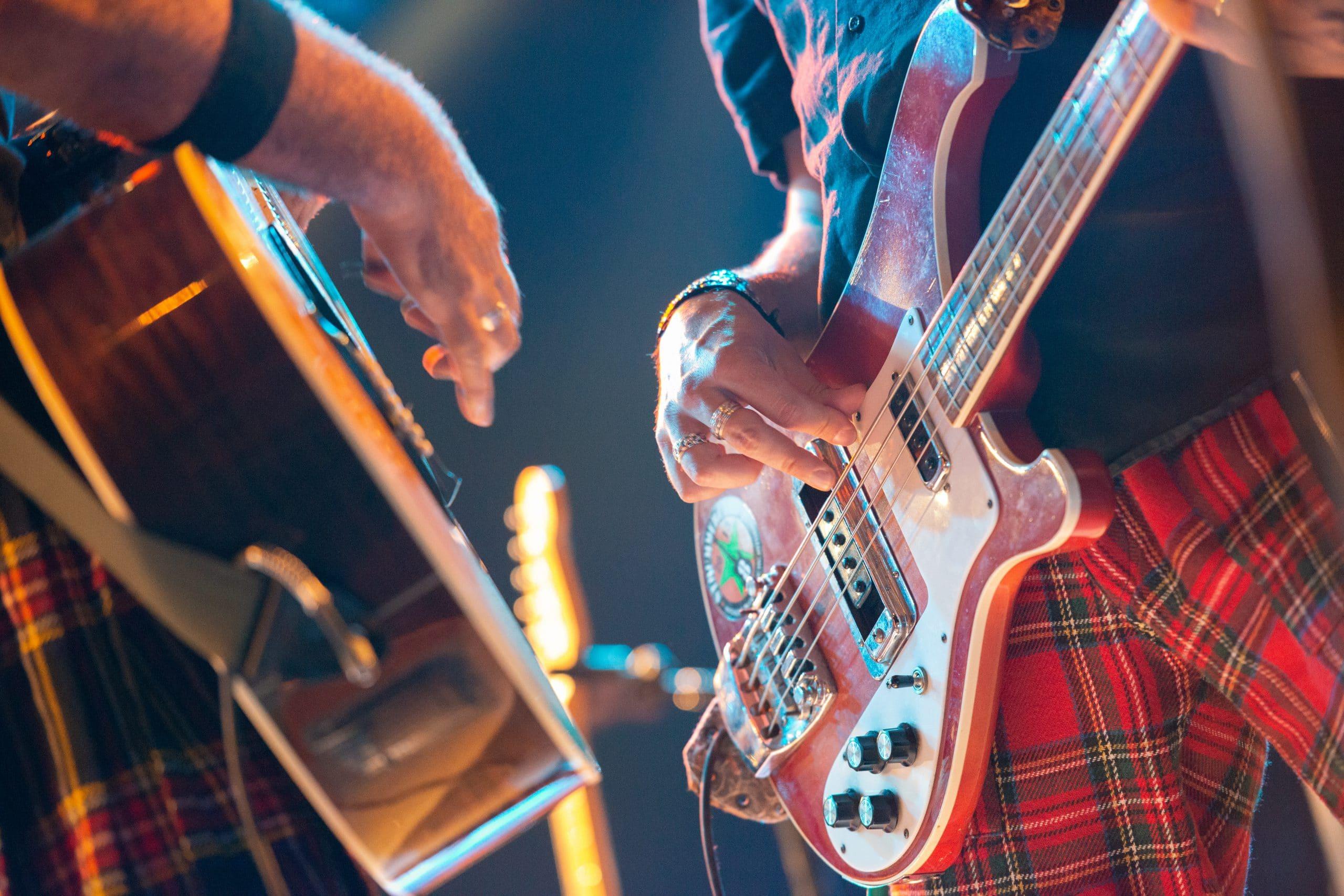 kitaristi ja basisiti soittavat yhdessä lavalla vastakkain, lähikuva soittimista