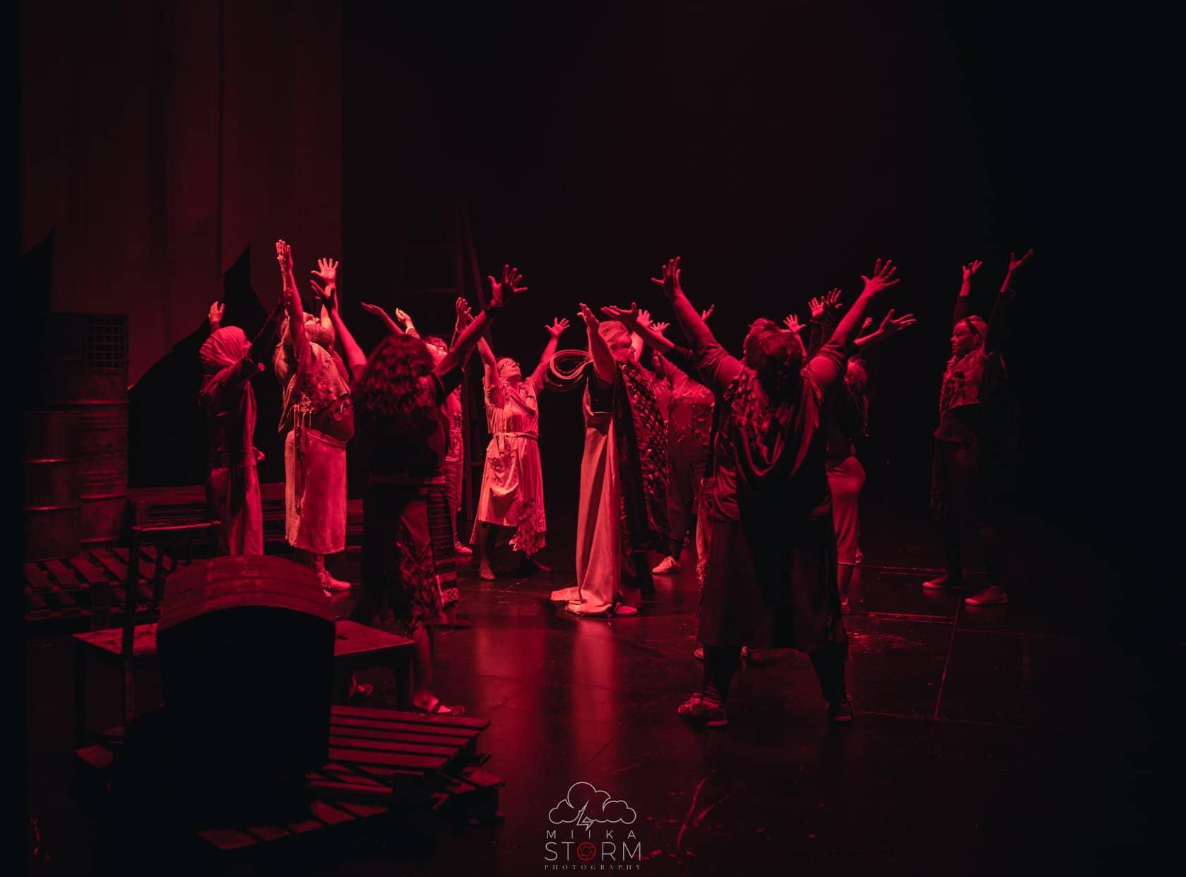 musikaaliryhmä ringissä kädet ylhäällä punainen valaistus