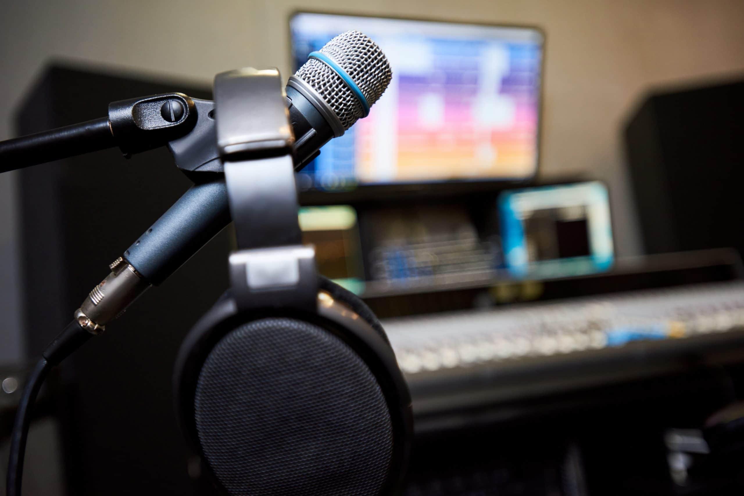 etualalla mikrofoni ja kuulokkeet, taustalla studio häivytettynä