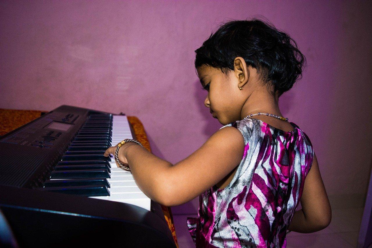 bändipaja, pikkutyttö soittaa syntetisaattoria vasemmalla kädellä