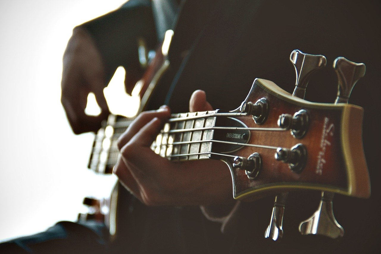 mies soittaa bassokitaraa, lähikuva basson kaulasta
